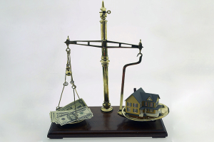 Scales weighing money against house